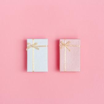 Minimalistyczna kompozycja z małymi pudełkami prezentowymi w kolorze różowym i białym. pocztówka z wyprzedaży, bony upominkowe, ulotka z miejscem na tekst. widok z góry i leżał płasko.