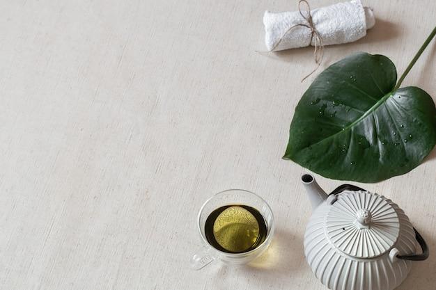 Minimalistyczna Kompozycja Z Zieloną Herbatą W Filiżance, Czajniczkiem I Akcesoriami Do Kąpieli. Pojęcie Zdrowia I Urody. Premium Zdjęcia
