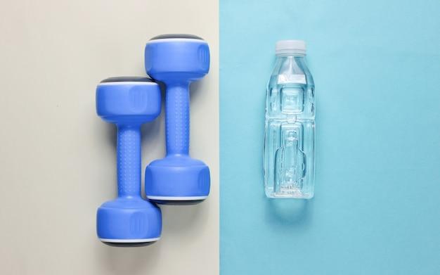 Minimalistyczna koncepcja fitness. hantle, butelka wody na kolorowym
