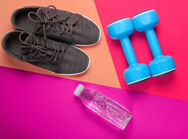 Minimalistyczna koncepcja fitness. hantle, trampki, butelka wody na kolorowym