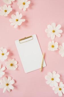 Minimalistyczna koncepcja w stylu. kwiaty rumianku białe stokrotki na jasnoróżowym tle z białymi tabletkami i złotym długopisem. kreatywny styl życia, koncepcja lato, wiosna