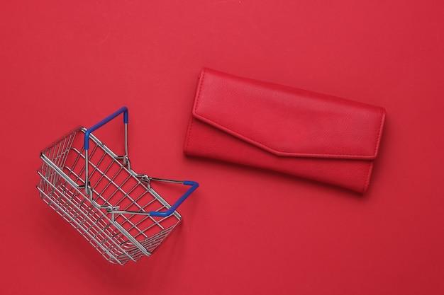 Minimalistyczna koncepcja zakupów mini kosz na zakupy i czerwony skórzany portfel na czerwonym tle