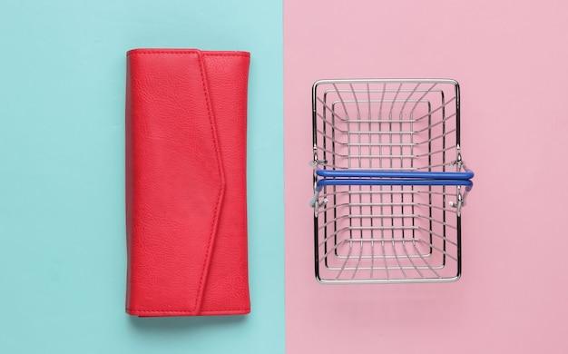 Minimalistyczna koncepcja zakupów mini kosz na zakupy i czerwony skórzany portfel na różowym niebieskim tle