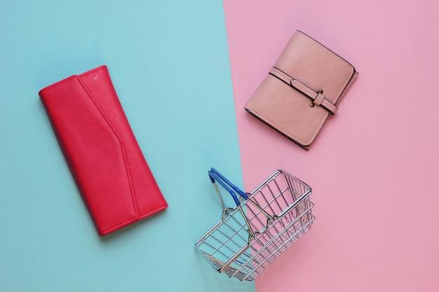 Minimalistyczna koncepcja zakupów mini kosz na zakupy i dwa portfele na różowym niebieskim tle