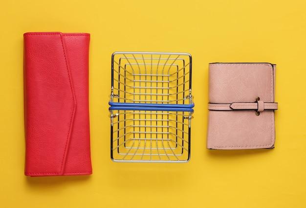 Minimalistyczna koncepcja zakupów mini kosz na zakupy i dwa portfele na żółtym tle