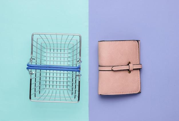 Minimalistyczna koncepcja zakupów mini kosz na zakupy i skórzany portfel na fioletowo-niebieskim tle