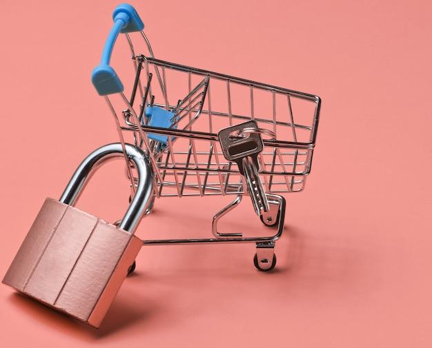 Minimalistyczna koncepcja zakupów. mini wózek sklepowy z zamkiem w kolorze różowym
