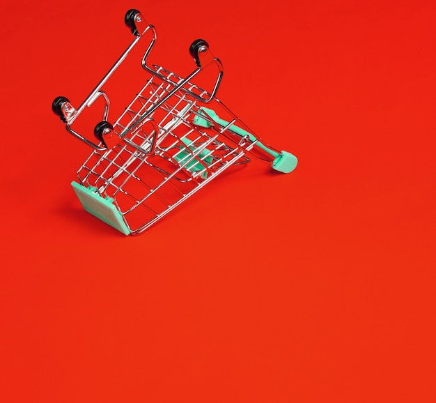 Minimalistyczna koncepcja zakupów. pusty odwrócony miniaturowy wózek na zakupy na czerwonym tle. skopiuj miejsce