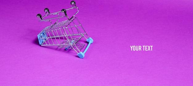 Minimalistyczna koncepcja zakupów. pusty odwrócony miniaturowy wózek na zakupy na fioletowym tle. skopiuj miejsce