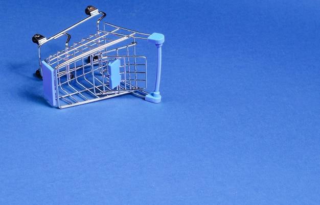 Minimalistyczna koncepcja zakupów. pusty odwrócony miniaturowy wózek na zakupy na niebieskim tle. skopiuj miejsce