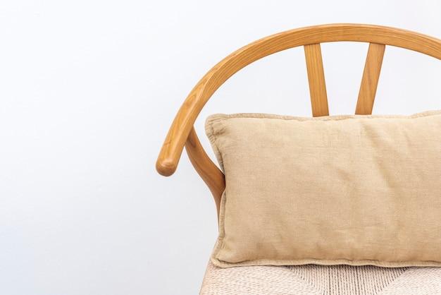 Minimalistyczna lniana poszewka na poduszkę w kolorze beżowym na krześle