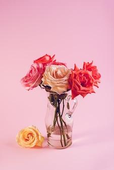 Minimalistyczna martwa natura z pojedynczą delikatną różową różą w wazonie na kolorowym tle