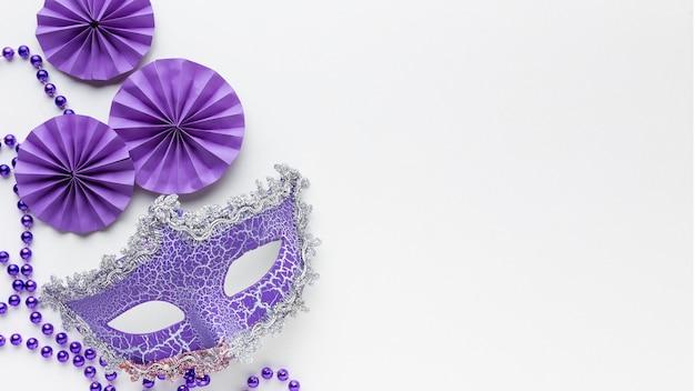 Minimalistyczna maska karnawałowa i fioletowe papierowe dekoracje