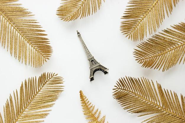 Minimalistyczna moda martwa. figurka wieży eiffla wśród ozdobnych złotych liści palmowych na białym tle. widok z góry