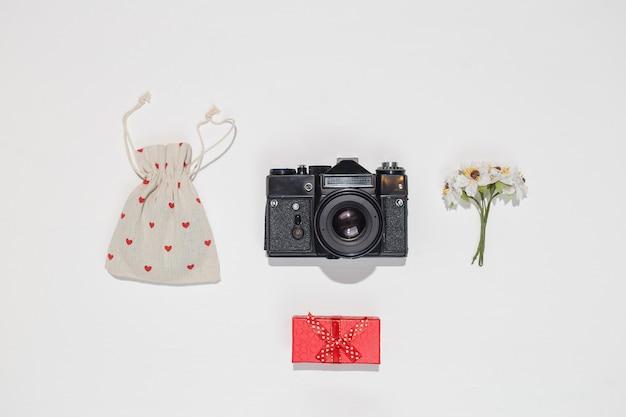 Minimalistyczna, płaska kompozycja z retro aparatem, czerwonym pudełkiem, płócienną torbą z czerwonymi kształtami serca i wiosennym kwiatem na białym tle. modna makieta płasko świecąca dla blogerów, projektantów, fotogr