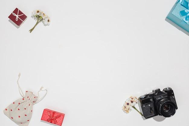 Minimalistyczna, płaska kompozycja z retro aparatem, czerwonymi i niebieskimi pudełkami prezentowymi, płócienną torbą z czerwonymi kształtami serca i wiosennym polem kwiatowym na białym tle. modna makieta z płaskim kloszem dla blogerów, projekt