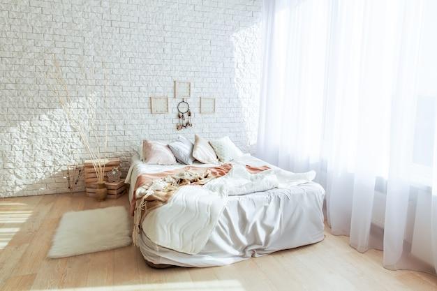 Minimalistyczna sypialnia z dużym łóżkiem i ceglaną ścianą