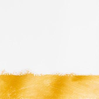 Minimalistyczna złota farba i białe tło