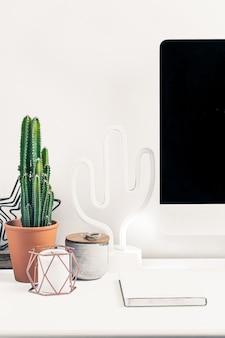 Minimalistyczne biurko z fantazyjnym białym komputerem, światłem kaktusa, zielonym kaktusem w ceramicznej doniczce.