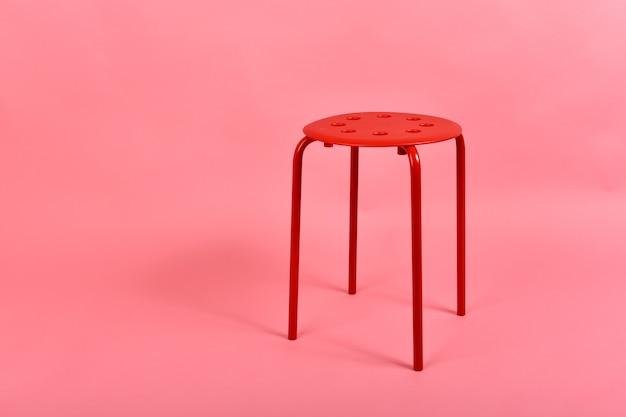 Minimalistyczne czerwone metalowe krzesło w stylu wnętrza na pastelowym różowym tle.