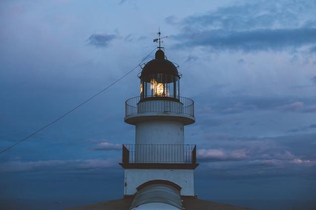 Minimalistyczne i geometryczne symetryczne ujęcie pięknej zabytkowej latarni morskiej na szczycie klifu