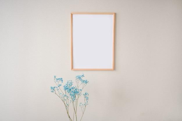 Minimalistyczne kobiece martwe natury w pastelowych kolorach. pusta ramka na plakat z makietą na beżowej ścianie, stylowa kompozycja z niebieskimi suchymi kwiatami