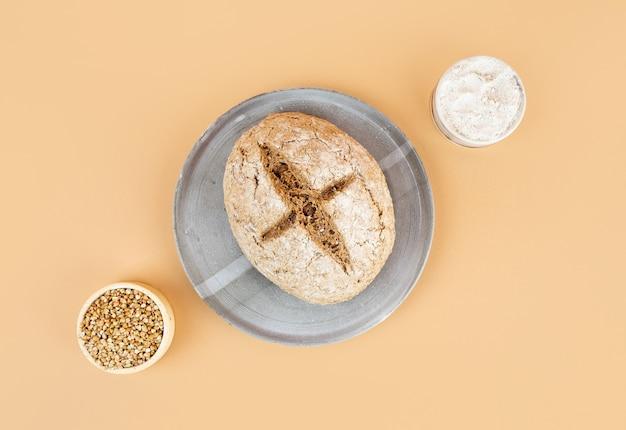 Minimalistyczne kreatywne beżowe tło z zielonym chlebem gryczanym. szary domowy talerz ceramiczny. nieszkodliwe, zdrowe, bezglutenowe zdrowe wypieki dla wegan. chleb alternatywny. kopiuj spase