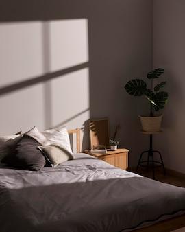 Minimalistyczne łóżko z rośliną wewnętrzną