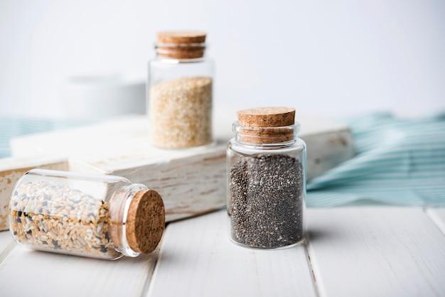 Minimalistyczne słoiki wypełnione zgniecionymi nasionami i drewnianą deską
