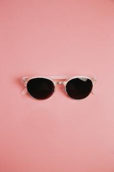 Minimalistyczne ujęcie pary okularów przeciwsłonecznych na pastelowo różowym tle, projekty i koncepcje letnie