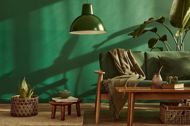 Minimalistyczne wnętrze salonu w stylowym domu z designerską aksamitną sofą, dywan na podłodze, brązowe drewniane meble, roślina, książka, lampa wisząca