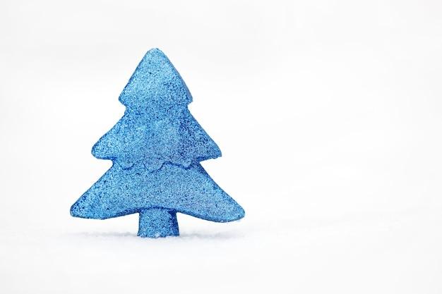 Minimalistyczne zdjęcie niebieskiego drzewa zabawki na prawdziwym śniegu w zimowy dzień.