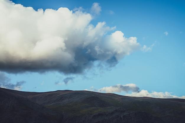 Minimalistyczny alpejski krajobraz z górską sylwetką pod zachmurzonym niebem z dużą chmurą. ciemna góra i jasne niebo. minimalne tło natura z sylwetką góry pod dużą chmurą w błękitne niebo.