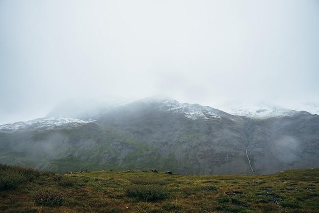 Minimalistyczny alpejski krajobraz z ośnieżonymi górami w pochmurnej pogodzie w deszczu. głęboki wąwóz na tle snowbound pasma górskiego pod niskim zachmurzonym niebem. nastrojowy minimalizm w wysokich górach.