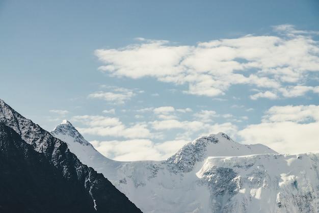 Minimalistyczny alpejski krajobraz z wysoką pokrytą śniegiem górą z ośnieżonym szczytem pod chmurami cirrus. piękna górska sceneria z wielkim śnieżnobiałym ostrym szczytem w zachmurzonym niebie. niesamowite góry.