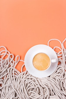 Minimalistyczny bawełniany biały linowy tło z filiżanką cappuccino na koralowym kolorowym tle.
