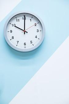 Minimalistyczny biały zegar ścienny z lekkim metalem na niebieskim białym tle. koncepcja czasu.