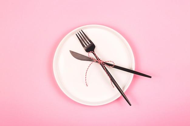 Minimalistyczny bożonarodzeniowy pojęcie z białym talerzem na różowym tle.