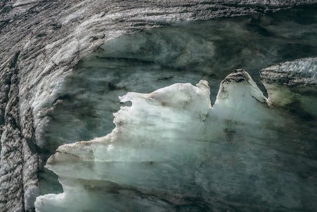 Minimalistyczny charakter tła powierzchni lodowca z pęknięciami i rysami. minimalne naturalne tło lodowej ściany i bloków lodu z lodowca z bliska. piękna natura tekstura lśniąca ściana lodowcowa.