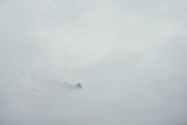 Minimalistyczny górski krajobraz z wysoką spiczastą skałą w chmurach. minimalistyczna górska sceneria z ostrym ośnieżonym szczytem górskim nad chmurami. śnieżnobiały spiczasty szczyt nad białymi chmurami. duży top w gęstej mgle