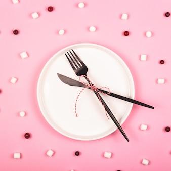 Minimalistyczny koncept bożonarodzeniowy z białym talerzem na różowo wśród wzoru składników.
