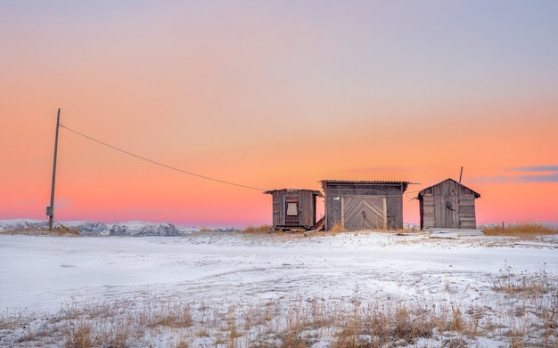 Minimalistyczny krajobraz. drewniane wędzarnie ryb w autentycznej miejscowości teriberka. półwysep kolski. rosja.