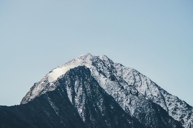 Minimalistyczny krajobraz górski z czarnym szczytem z białym śniegiem pod błękitnym niebem. pokryty śniegiem spiczasty szczyt w słońcu. nastrojowa górska sceneria ze szczytem w słońcu. niesamowity szczyt góry.