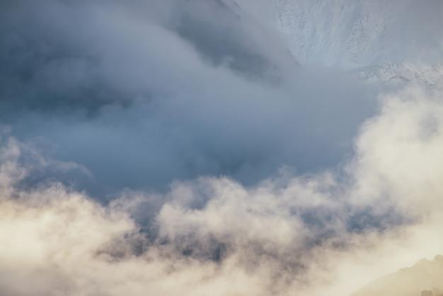 Minimalistyczny krajobraz górski z wysokim ośnieżonym murem górskim w grubych niskich chmurach w złotym słońcu. niesamowita minimalistyczna sceneria z gęstymi, niskimi chmurami w złotym słońcu i wielkimi ośnieżonymi górami.