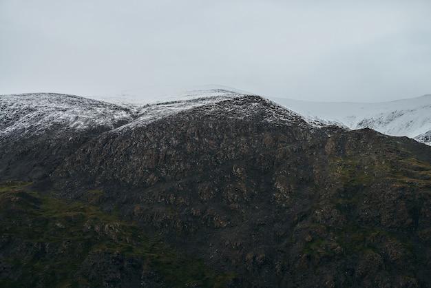 Minimalistyczny krajobraz wyżyny z ośnieżonymi górami pod zachmurzonym niebem. wysokie góry pokryte śniegiem w pochmurną pogodę. nastrojowy minimalizm z zielonymi górami, białym śniegiem i szarym niebem.