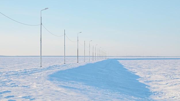 Minimalistyczny krajobraz z latarniami ulicznymi wzdłuż wiejskiej drogi w zaśnieżonym polu w pastelowych kolorach
