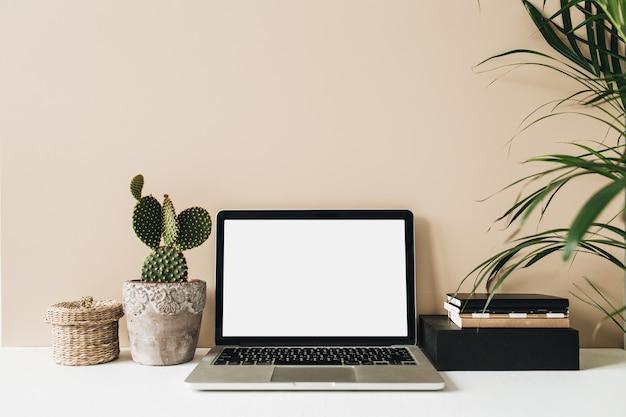 Minimalistyczny obszar roboczy biurka domowego z laptopem, kaktusem i palmą na beżowym tle