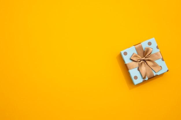 Minimalistyczny opakowany prezent na żółtym tle