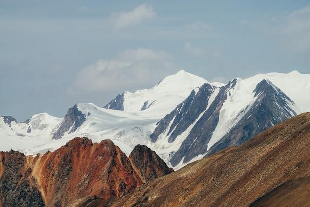 Minimalistyczny piękny alpejski krajobraz z ogromną zaśnieżoną górą za jaskrawą czerwoną, skalistą ścianą.
