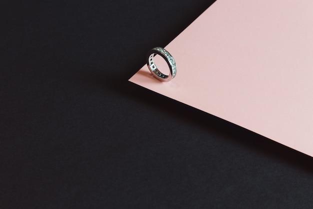 Minimalistyczny pierścionek z brylantem na różowo-czarnym tle